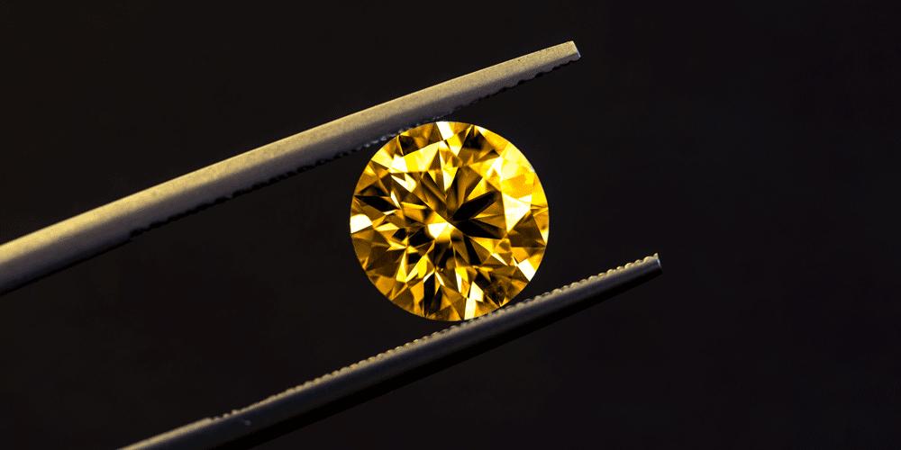 Golden schimmernder Diamant mit Pinzette gehalten